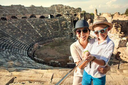 Mutter mit Sohn lächelt in die Kamera und macht ein Selfie-Foto im antiken Theater mit einem Selfie-Stick. Reisen um die Welt mit Kinderkonzeptbild.