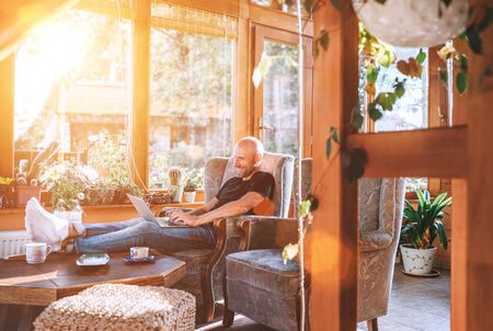Man dressed black T-shirt and jeans sitting in a comfortable armchair, using a modern slim laptop and drinking tea in house sunroom living room. Distance or freelance or writer working concept image.