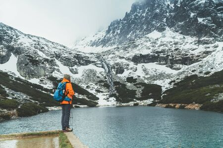 Dressed bright orange jacket female backpacker enjoying the Velicke pleso (mountain lake) view as she have mountain walk in Velicka valley in High Tatras, Slovakia. Active people in nature concept.
