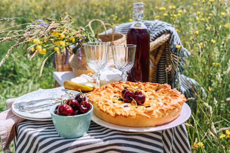 Table view served with beautiful vintage wine glasses and sweet cherry pie with fresh cherries