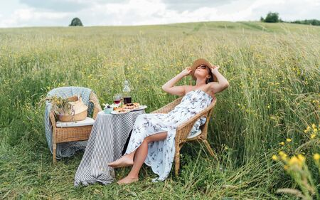 Young Woman dressed light summer dress and straw hat sitting in a rattan chair on the high green grass meadow and enjoying the moment near the picnic table with red wine and homemade pie.