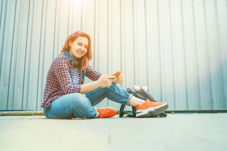 Beautiful modern smiling young female teenager in a checkered shirt and jeans with headphones and smartphone sitting on the street sidewalk. Modern teens in digital world concept image 免版税图像