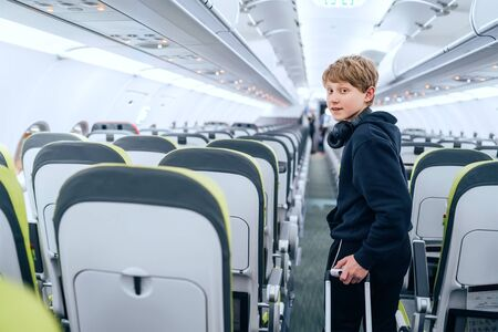 Smiling blonde hair teenager portrait staying in aircraft corridor with headphones with cabin trolley bag. Kids traveling or unaccompanied child in aircraft concept image. 免版税图像