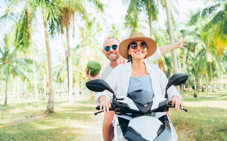 Happy smiling couple travelers riding motorbike scooter under palm trees. Laughing man carrying a coconut in hand.Tropical vacation concept image 免版税图像