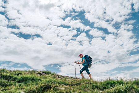 Female backpacker climbing to the mountain top using trekking poles with bright cloudscape background. Active vacation spending by sporty people concept horizontal image. 免版税图像