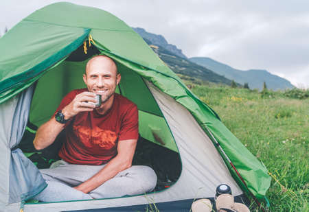 Sincerely smiling Man in the green tent drinking the coffee  with mountain background early foggy morning scene. Active people enjoying traveling with tents concept image.