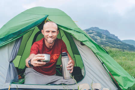 Smiling Man in the green tent drinking the tea  with mountain background. He offering a teacup to the cameraman. Active people enjoying traveling with tents concept image.