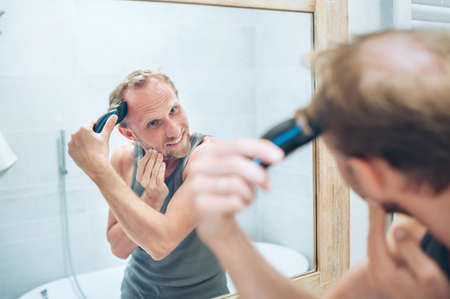 Body and skincare treatment concept. Smiling Man making new style haircut trimming a hairs using an electric rechargeable Trimmer looking in bathroom mirror. Hairstyle 免版税图像