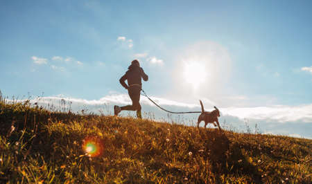 Man runing with his beagle dog at sunny morning. Healthy lifestyle and Canicross exercises jogging concept image. 免版税图像
