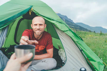 Smiling bald Man in the green tent taking the flask teacup for morning tea-drinking with mountain background. Active people enjoying traveling with tents concept image.