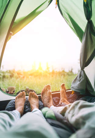 Inside the green touristic tent vertical view of the barefoot couple's legs. Man and woman lying close to each other and enjoying sunrise sunrays.Active people enjoying traveling with tents concept. 免版税图像