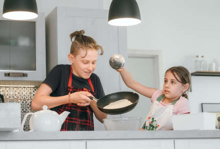 Sister and Brother dressed aprons making a homemade pancakes on the home kitchen. Girl poring a liquid dough on the hot pan. Kids Home cooking concept image.