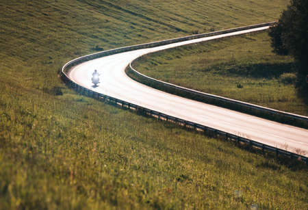 Motorcycle with headlight moving by the highway illuminated with back evening sun light. Safety solo traveling concept image. 免版税图像