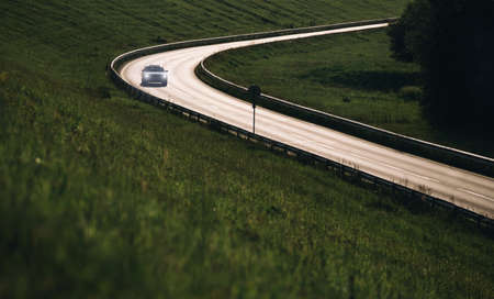 Fast modern car moving by the highway illuminated with back evening sun light. Safety auto traveling concept image.