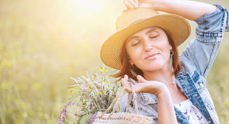 Young woman sunny portrait closed the eyes and enjoying the sun rays. She dressed a jeans jacket, straw hat and light summer dress. She picked a wildflowers on meadow and carrying bouquet in basket