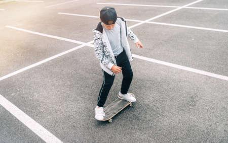 Teenager skateboarder boy with a skateboard on asphalt playground doing tricks. Youth generation Freetime spending concept image.
