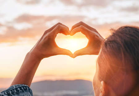 Young female making a HEART shape with her fingers catching the sunset beams with spectacular sky background. Love or human and nature concept image.