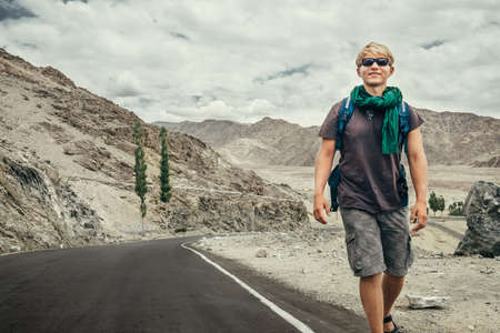 Traveler young man walking by the mountain road in Indian Himalaya mountains. Traveling around the world concept image.