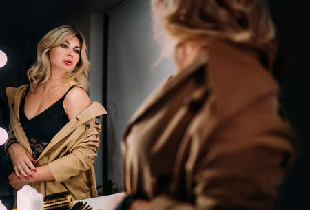 Sensual portrait of middle aged seductive woman in Trench coat gazing at mirror reflection appreciating her hair style. Human emotion or clothing fashion concept image. Back view selective focus shot.