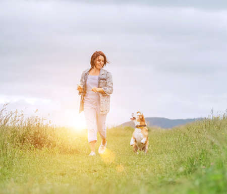 Happy jogging smiling female with fluttering hairs and her beagle dog running and looking at eyes. Walking by meadow grass path in nature with pets, healthy active people lifestyle concept image. 免版税图像
