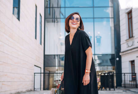 Beautiful modern middle-aged female laughing at camera Portrait dressed black dress and sunglasses with shopping bags near the shopping center. Natural beauty people's everyday concept image. 免版税图像