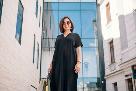 Beautiful modern middle-aged female smiling at camera Portrait dressed black dress and sunglasses with shopping bags near the shopping center. Natural beauty people's everyday concept image. 免版税图像