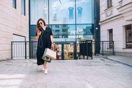 Smiling beautiful modern middle-aged female Portrait dressed black dress and sunglasses with shopping bags browsing slim smartphone listening music with wired earphones. Beautiful people concept image