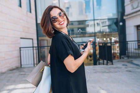 Beautiful modern middle-aged female Smiling Portrait dressed black dress and sunglasses with shopping bags holding slim smartphone listening music with wired earphones. Beautiful people concept image.