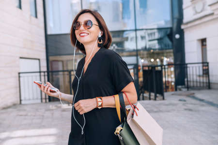 Smiling beautiful modern middle-aged female Portrait dressed black dress and sunglasses with shopping bags holding slim smartphone listening music with wired earphones. Beautiful people concept image.