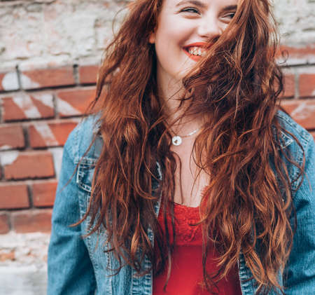 Sincerely smiling Red curled hair caucasian teen girl with applied red lipstick lips with blue eyes fashion vertical portrait on the red brick wall background. Natural people beauty concept image.