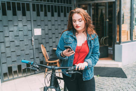 Portrait of red curled long hair caucasian teen girl on the city street walking with bicycle using the smartphone with earphones. Natural people beauty urban life concept image.