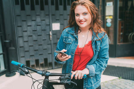 Red curled long hair caucasian teen girl on the city street walking with bicycle using the smartphone with earphones fashion portrait. Natural people beauty urban life concept image.