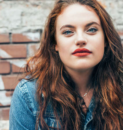 Red curled hair caucasian teen girl with applied red lipstick lips with blue eyes fashion portrait on the red brick wall background. Natural people beauty concept image.