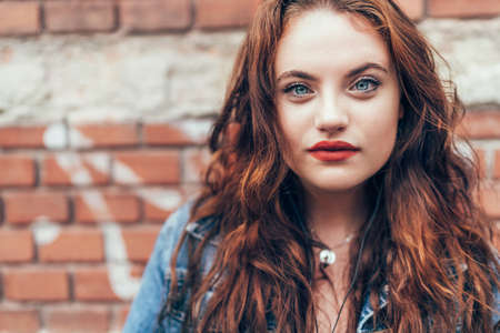 Fashion portrait of red curled long hair caucasian teen girl with applied red lipstick lips with blue eyes with a red brick wall background. Natural people's beauty concept image. 免版税图像