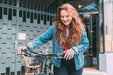 Red curled long hair caucasian teen girl on the city street walking with bicycle fashion portrait. Natural people beauty urban life concept image.