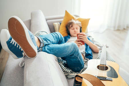 Preteen boy lying with guitar on cozy sofa dressed casual jeans and new sneakers listening to music and chatting using wireless headphones connected with a smartphone. Using electronic devices concept 免版税图像