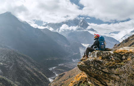 Young hiker female backpacker sitting on the cliff edge and enjoying mountain peaks view during Everest Base Camp (EBC) trekking route near Phortse, Nepal. Active vacations image concept 免版税图像