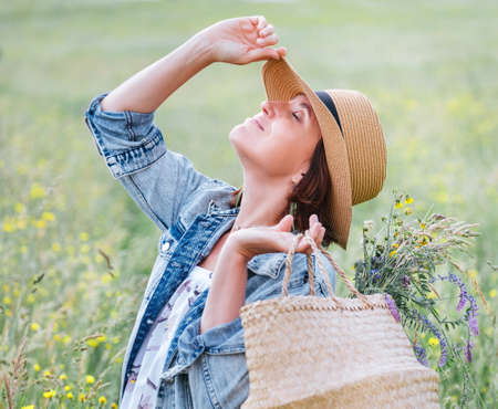 Young Woman portrait closed the eyes and enjoying the sun rays. She dressed a jeans jacket, straw hat and light summer dress. She picked a wildflower on meadow and carrying bouquet in basket.