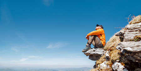 Active people and European tourism concept image. Dressed bright orange jacket hiker in baseball cap and sunglasses sitting on rocky cliff enjoying green valley at Mala Fatra mountain range,Slovakia.
