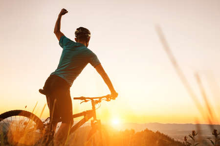 Young Man biker man meets a sunset in top of hill. He rising a one arm greeting on another successful day ending. Active sport people concept image