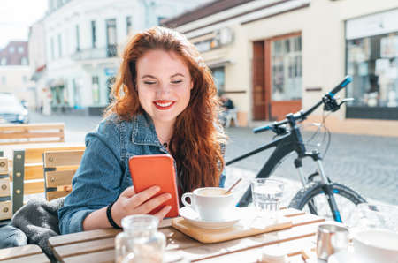 Portrait of smiling red curled long hair caucasian teen girl sitting on a cozy cafe outdoor terrace on the street using the modern smartphone. Young woman taking a break in her city bicycle tour.