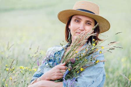 Portrait of a calm young woman with wildflowers bouquet. She dressed a jeans jacket, straw hat, and summer light dress. Natural people's beauty in the nature concept image. 写真素材