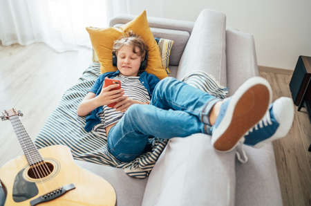 Preteen boy lying with guitar on cozy sofa dressed casual jeans and new sneakers listening to music and chatting using wireless headphones connected with a smartphone. Using electronic devices concept