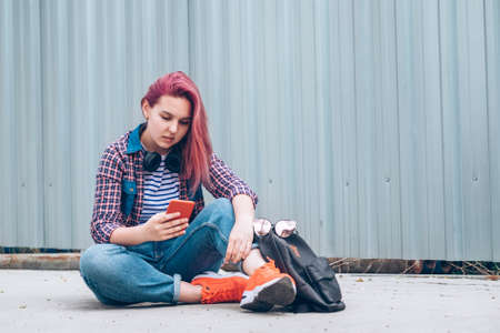 Beautiful modern young female teenager in a checkered shirt and jeans with headphones and a smartphone sitting on the street sidewalk. Modern teens in the digital world concept image 版權商用圖片