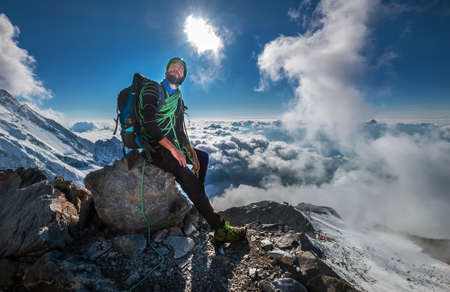 Climber in a safety harness, helmet, and high mountaineer boots with picturesque clouds background sitting at 3600m altitude on big rock and looking at summit during Mont Blanc ascending, France route