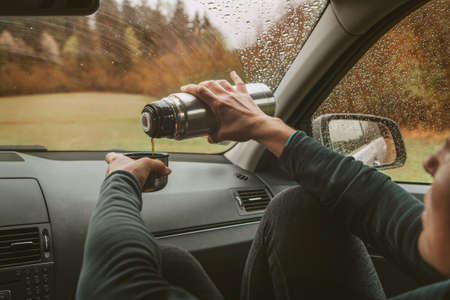 Female pouring the hot tea in tourist flask mug. She sitting on co-driver seat inside modern car, enjoying the moody rainy day weather looking through windscreen drops. Auto journeys concept image. Standard-Bild