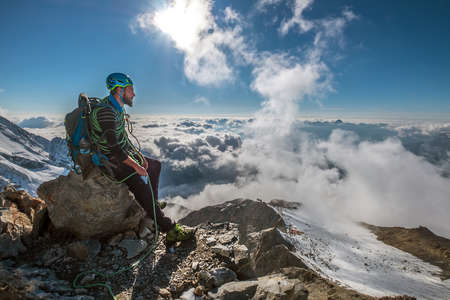 Bearded Climber in a safety harness, helmet, and on body wrapped climbing rope with sitting at 3600m altitude on a cliff and looking at  picturesque clouds during Mont Blanc ascending, France route Standard-Bild