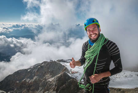 Smiling Climber in a safety harness, helmet, and  on body wrapped climbing rope with picturesque clouds background showing thumb sign at 3600m altitude during Mont Blanc ascending, France route