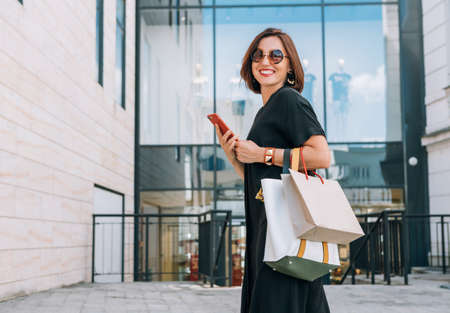 Beautiful modern middle-aged female Smiling Portrait dressed black dress and sunglasses with shopping bags holding a slim smartphone going to a mall. Beautiful people concept image.