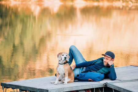 Man dog owner and friend beagle dog on the wooden pier on the mountain lake and enjoying the landscape and each other's company during their walking in the autumn season time. Human and pet concept.
